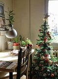 Christmas morning. In the workroom. Scene with Christmas tree and desk with flowers on it Stock Photography