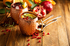 Christmas Moscow mule with pomegranate and orange. In a rustic setting Stock Image