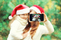 Christmas mother and child taking picture self portrait on smartphone together, closeup, blurred background Royalty Free Stock Image