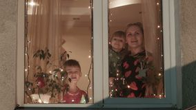 Christmas, mother and children run up to a window and look at the sky. Mother and children celebrate Christmas, look through a window at the street stock footage