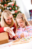 Christmas: Mother Helps Girl With Icing For Gingerbread Decorati Stock Images
