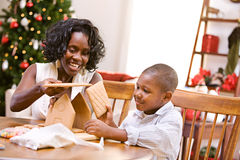 Christmas: Mother And Son Build Holiday Gingerbread House. African American mother and child celebrate Christmas with a Christmas tree, gingerbread house and stock photography