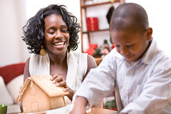 Christmas: Mother And Son Build Holiday Gingerbread House. African American mother and child celebrate Christmas with a Christmas tree, gingerbread house and royalty free stock photos