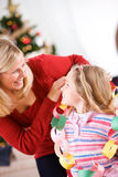 Christmas: Mother Wraps Paper Chain Garland Around Girl Royalty Free Stock Photo