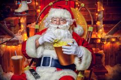 Christmas movie concept. Santa Claus sitting on his armchair eating popcorn, drinking soda and watching a Christmas movie. Entertainment and cinema concept royalty free stock photo
