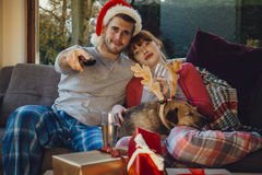 Christmas Movie Night. Young couple at home with their pet dog at Christmas time. They are all cuddled up on the sofa at home, watching television Stock Photo