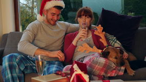 Christmas Movie Time. Young couple at home with their pet dog at Christmas Time. They are watching a movie and drinking glasses of champagne