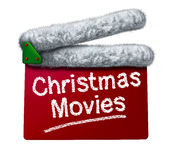 Christmas Movies. And holiday classic cinema and TV flicks with a red clapperboard and a Santa Clause hat white fur trim as an entertainment symbol of the Royalty Free Stock Photography