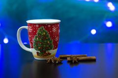 Christmas Mug with Hot Drink. Christmas Mug on a table with background lights Royalty Free Stock Images