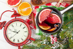 Christmas mulled wine and alarm clock on wooden table Stock Photo