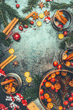 Christmas mulled wine background. Cooking pot and mugs with mulled wine, fir brunches, festive decoration and spices, top view Stock Image