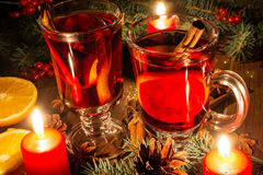 Christmas mulled wine in the candle light. Christmas mulled wine with spices and orange in the candle light. festive romantic drinks background Stock Images