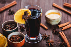 Christmas mulled wine with cinnamon, anise stars, honey and orange slices on wooden background Stock Photo