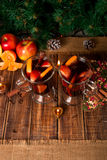 Christmas mulled wine with fruits, candles  and spices on wooden table. Xmas decorations in background. Two glasses. Winter warmin Stock Photo