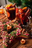 Christmas mulled wine with fruits and spices on wooden table. Xmas decorations in background. Two glasses. Winter warming drink  r Royalty Free Stock Photo