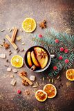 Christmas mulled wine or gluhwein with spices and orange slices on rustic table top view. Traditional drink on winter holiday. Stock Photos