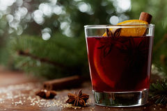 Christmas mulled wine or gluhwein with spices and orange slices on rustic table, traditional drink on winter holiday, magic light Royalty Free Stock Photography