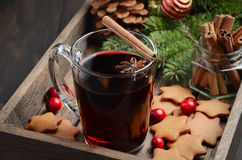 Christmas mulled wine. Holiday concept decorated with Fir branches, Gingerbread Cookies and Cranberries on dark wooden tray. Royalty Free Stock Photo
