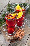 Christmas mulled wine with spices and snowy fir tree Stock Photography