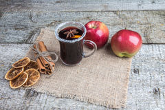Christmas mulled wine, spices and two apples on sackcloth. Royalty Free Stock Images
