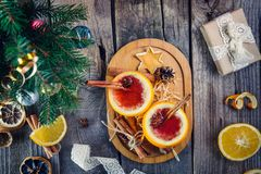 Christmas mulled wine - unusual served in orange. Hot winter drink with berries, orange,spices, cinnamon on old wooden table with Royalty Free Stock Image