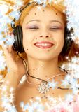 Christmas music #3. Christmas picture of smiling redhead listening music with snowflakes stock photography