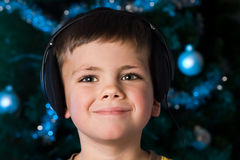 Christmas music boy. Young boy listening to music in front of a christmas tree Royalty Free Stock Images
