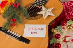 Christmas music card background with guitar and holiday winter d. Ecorations for text stock photography