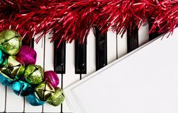 Christmas music concept. Blank paper on the piano with jingle bells and red tinsel royalty free stock photo