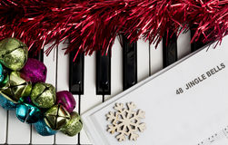 Christmas music concept. Printed music on the piano with jingle bells, snowflake and spangle Royalty Free Stock Photos