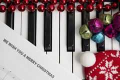 Christmas music concept. Printed music on the pianto with jingle bells, red christmas balls and hat Royalty Free Stock Images
