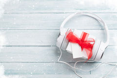 Christmas music gift. Concept. Headphones and gift box on wooden table. Top view with copy space royalty free stock images