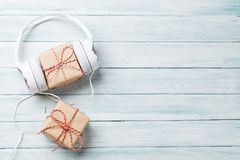 Christmas music gifts. Christmas music gift concept. Headphones and gift boxes on wooden table. Top view with copy space royalty free stock photos