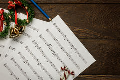 Christmas music note paper with Christmas wreath on wo. Top view Christmas music note paper with Christmas wreath on wooden background and copy space royalty free stock photo