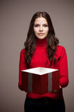 Christmas mystery. Portrait of a beautiful young brunette woman holding gift box with mysterious light Stock Photo