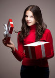 Christmas mystery. Portrait of a beautiful young brunette woman holding gift box with mysterious light Stock Photography