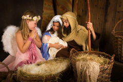 Christmas nativity with angel. Little 7 year old angel visiting a nativity scene reenacted with a doll Stock Image
