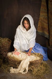 Christmas nativity baby. Teenager girl playing the role of the Virgin Mary with a doll in a live Christmas nativity scene royalty free stock image