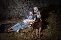 Christmas nativity barn. Live Christmas nativity scene in an old barn - Reenactment play with authentic costumes. The baby is a property released doll royalty free stock image