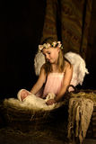 Christmas nativity at night. Pink little girl playing an angel in a Christmas nativity scene with a doll royalty free stock image