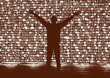 Christmas nativity story words illuminated. Melbourne, Australia - December 28,2012: Silhouette of a man standing with arms raised in front of an illuminated royalty free stock image
