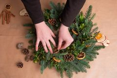 Christmas natural wreath. Florist s hands making natural Christmas wreath, christmas decorations with natural fir branches. Close up stock image