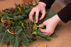 Christmas natural wreath. Florist s hands making natural Christmas wreath, christmas decorations with natural fir branches. Close up stock photography