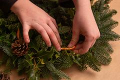 Christmas natural wreath. Florist s hands making natural Christmas wreath, christmas decorations with natural fir branches. Close up stock images
