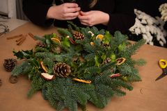 Christmas natural wreath. Florist s hands making natural Christmas wreath, christmas decorations with natural fir branches. Close up royalty free stock photo