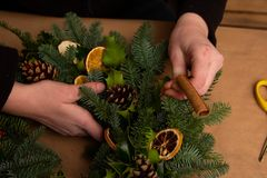 Christmas natural wreath. Florist s hands making natural Christmas wreath, christmas decorations with natural fir branches. Close up royalty free stock images