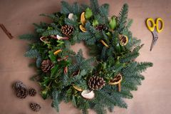 Christmas natural wreath. Florist s hands making natural Christmas wreath, christmas decorations with natural fir branches. Close up stock photos