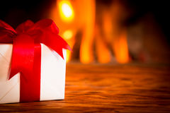 Christmas near fireplace. Christmas gift box on wood table against fireplace. Winter holiday concept Stock Images