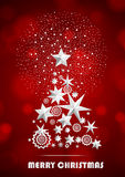 Christmas and New Year abstract with Christmas Tree made of stars and snowflakes with firework on red ambient blurred background Royalty Free Stock Photo