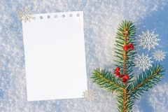 Christmas and new year background. blank white sheet of paper for text, greetings on natural snow with a blue tint. In the winter, decorated with snowflakes Royalty Free Stock Image